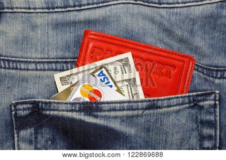 KHARKIV, UKRAINE - MARCH 16, 2016: American dollars, passport, credit cards Visa and Mastercard sticking out of the pocket of jeans