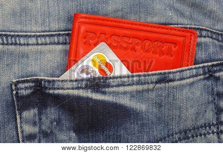 KHARKIV, UKRAINE - MARCH 16, 2016:  Passport, credit cards Mastercard sticking out of the pocket of jeans