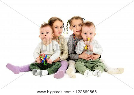Having twins twice. Two pairs sets of twin baby and twin children. Identical twin sisters are hugging identical twin brothers.