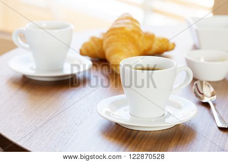 Two cups of coffee with croissants.