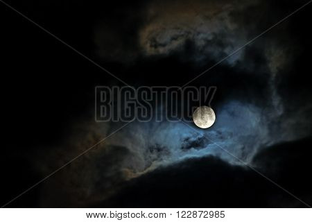 full moon lights up the clouds on the dark night sky copy space in the black background