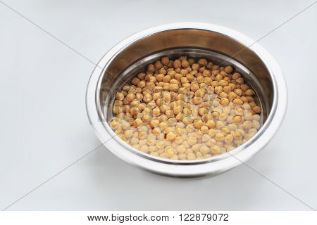 Chick-peas in water. Chick-peas in a bowl - close up photo
