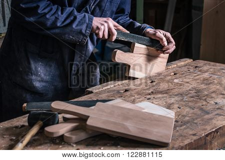 Carpenter Sanding Piece Of Timber With Sandpaper