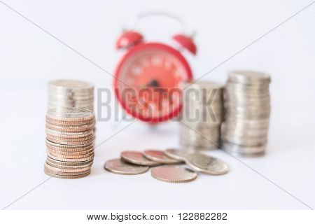 selective focus on coins front of blur red alarm clock concept to work at make money.