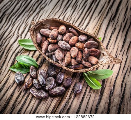 Cocoa pod and cocoa beans on the wooden table. poster