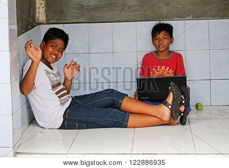 YOGYAKARTA/INDONESIA - CIRCA NOVEMBER 2015: Children smoking on the streets of South Yogyakarta. With approximately 57 million smokers Indonesia is the fifth largest tobacco market in the world