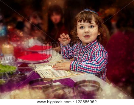 TEL AVIV ISRAEL - APRIL 3: Little boy at the celebration seder passover reading the Haggadah in Tel Aviv, Israel on April 3, 2015