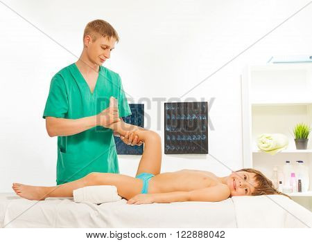 Smiling boy lying on the massage table an d doing exercises for his legs