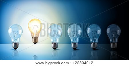 Idea concept with light bulbs sequence on a glass table with a lighted bulb on a blue background. Horizontal composition Front view