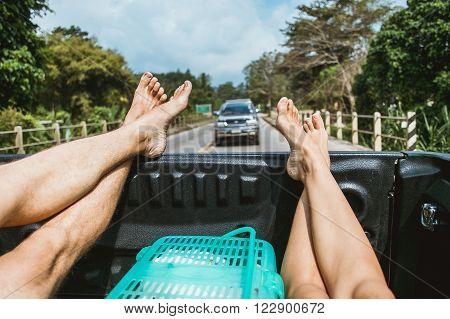 Legs of two hitchhiker man and woman traveling in pickup car with the road view on background