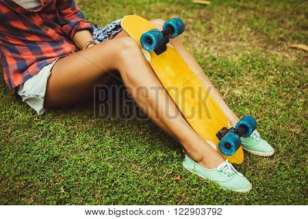 Legs of skateboarder girl sit on the grass in checkered shirt with her skateboard