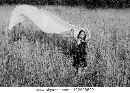 Black and white image of a pretty woman wearing a black dress with a length of white fabric flowing behind her.