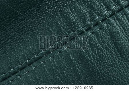 Green leather background. Diagonal stitch detail, close up