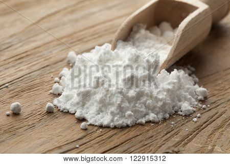 Wooden scoop with Vetsin on white background