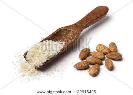 Wooden spoon with almond meal and almonds on white background