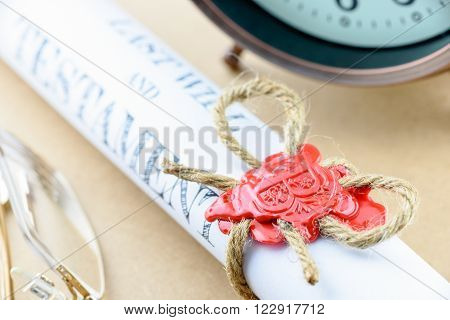 Rolled up scroll of last will and testament fastened with natural brown jute twine hemp rope sealed with sealing wax and stamped with alphabet letter B. Decorated with an antique clock and glasses.