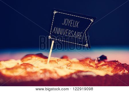 closeup of a black flag-shaped signboard with the text joyeux anniversaire, happy birthday in french topping a cake