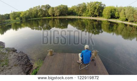 The boy with a fishing pole sitting on a wooden pier, aerial view