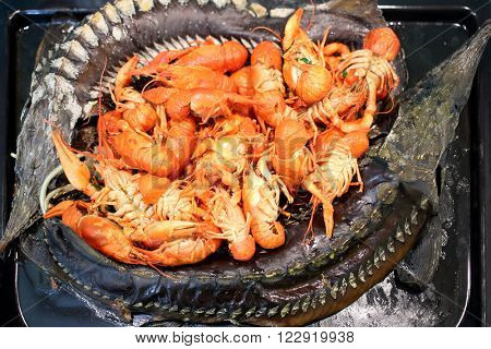 Baked sturgeons and crayfish on a black pan, close-up