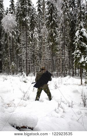 Man with hunter rifle in hands walking through the winter forest looking for animals.