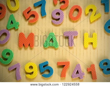 Colorful of math word and numbers on vintage brown background. Mathematics education concept background.