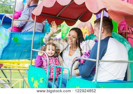 Cute little girls with their mother and father enjoying ride at fun fair, young family, amusement park poster