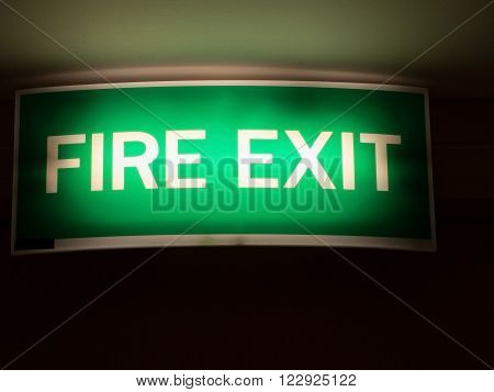 Fire exit sign. Light green emergency fire exit sign in the office/hotel shows people way out.