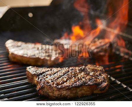 bone-in new york strip steaks cooking over flaming grill