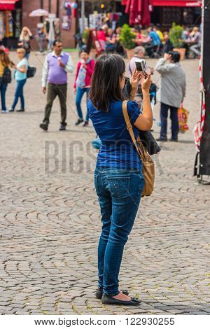 Back Side Of Young Woman Taking A Photo With Her Camera