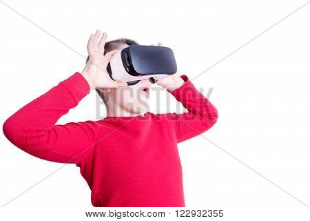 Fascinated male child in red long sleeve shirt holding and looking through virtual reality glasses over white background poster