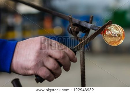 Glass blower forming beautiful piece of glass. A glass crafter is burning and blowing an art piece.