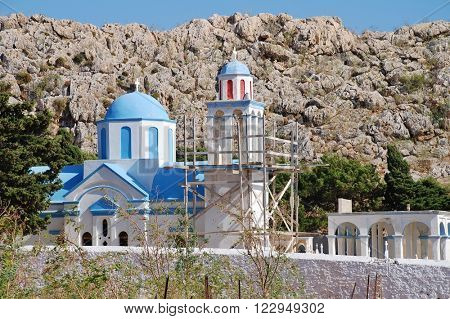 The domed church at the cemetery in Emborio on the Greek island of Halki. The bell tower is supported by scaffold due to cracking.