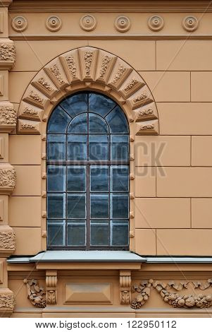 Window with arch and a bas-relief on a background of beige wall. From the series window of Saint-Petersburg.