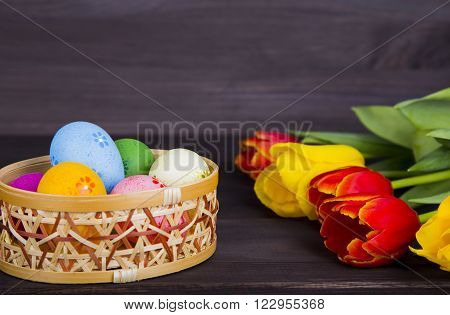 Colorful Easter Eggs In Wicker Basket With Tulips On Dark Wooden Background