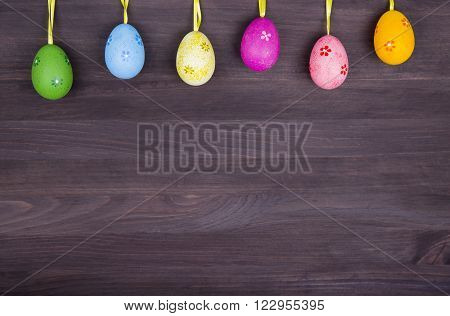 Colorful Easter Eggs Hanging On Dark Wooden Background