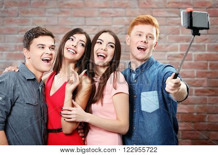 Teenager friends making photo by their self with mobile phone on brick wall background