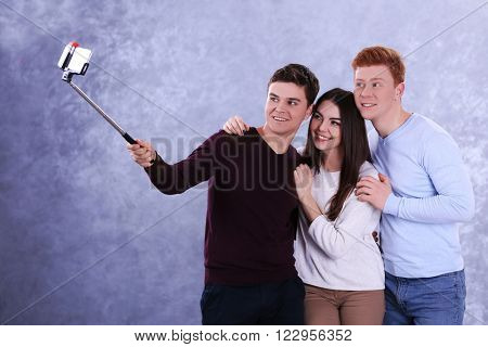 Teenager friends making photo by their self with mobile phone on grey background
