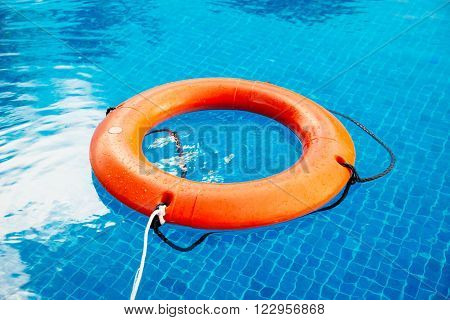 Life buoy afloat in a pool with blue clear water