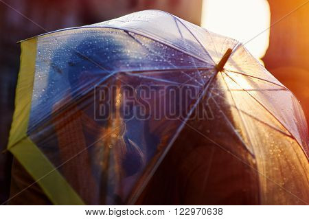 Closeup of young beautiful couple kissing under the umbrella in an autumn rainy day poster