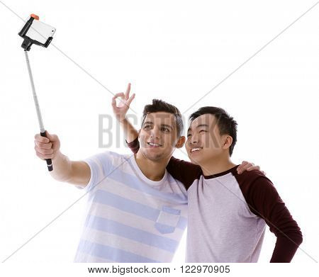 Two young men taking selfie with mobile phone isolated on white