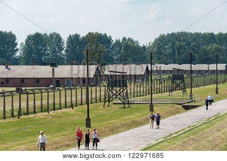OSWIECIM, POLAND - JULY 3, 2009: Auschwitz II - Birkenau Sector I barracks and watch towers with inner perimeter electrified fence