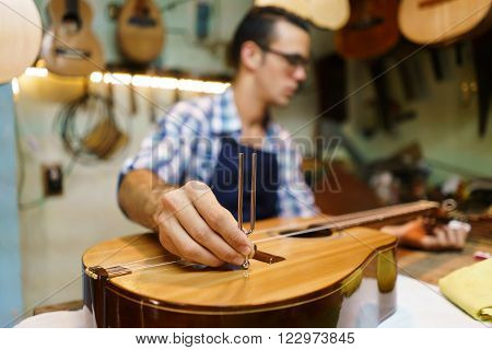 Lute maker shop and classic music instruments: young adult artisan fixing old classic guitar tuning the instrument with a metallic diapason. Closeup of hand on guitar body