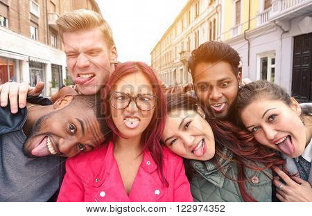 Multiracial best friends taking selfie outdoors in urban contest - Happy young people having fun together - Multi ethnic and Friendship concept - Soft vintage warm filtered look - Soft focus on faces