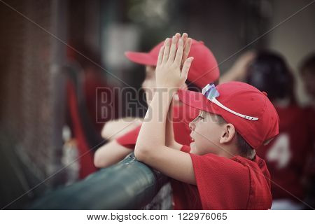 Baseball team in the dugout, cheering for their team, shallow focus, focus on hat.