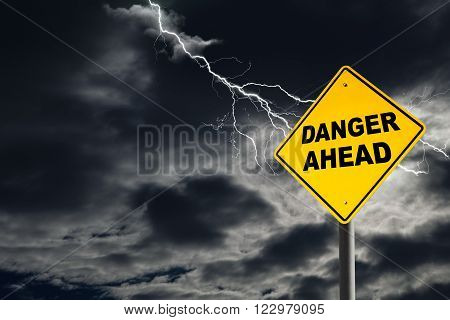 Danger Ahead road sign against a dark cloudy and thunderous sky. Conceptually warning of danger ahead.