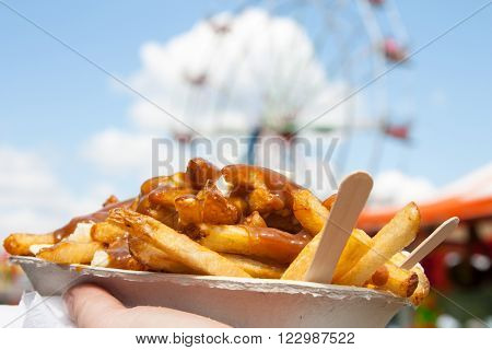 Poutine a Canadian favorite at the fair where junk food reigns supreme held up in front of the ferris wheel