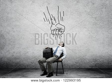 Businessman with suitcase sitting in chair under drawn fist