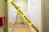 Yellow wet paint caution tape across a doorway with construction ladder in the background poster