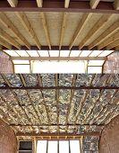 Fiberglass batt insulation between roof trusses at a house construction site poster