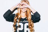 Love. Closeup portrait smiling happy young woman with long blon hair, making heart sign, symbol with hands white wall background. Positive human emotion expression feeling life perception attitude body language. Indoor. Warm color. Hipster. poster